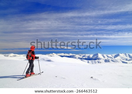 Ski mountaineer isolated on snow covered plateau surrounded by mountains #266463512