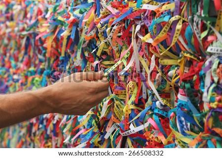 Tourist hand touching colorful Senhor do Bonfim ribbons at Pelourinho in Salvador, Bahia, Brazil.