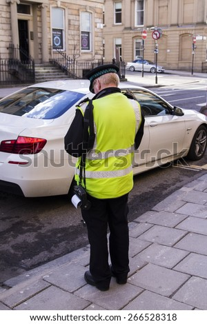 POLICEMAN,SHOT FROM BACK, GIVING A TICKET FOR BAD PARKING OR NOT PAYING TAX ,IN A SUNNY DAY IN STREETS OF UK