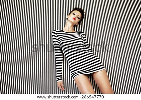 fashion woman in striped dress on striped background in studio #266547770