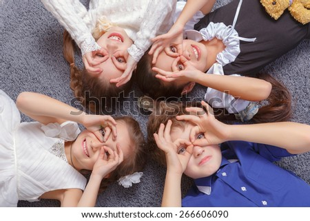 Having fun together. Group of happy diversity looking kids lying in star shape on the floor #266606090