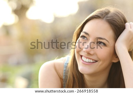Woman with white teeth thinking and looking sideways in a park in summer #266918558