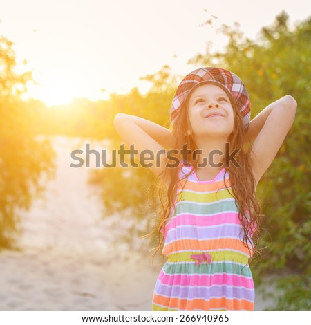 Beautiful little girl in hat on sunset background.