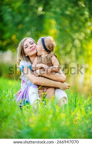 Portrait of smiling beautiful young woman and her little daughter sitting on grass, against green of summer park. #266947070