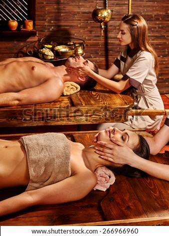 Couple  having oil Ayurveda spa treatment. Wooden table.Facial massage. #266966960