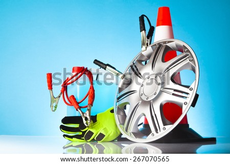 Car accessories - washer fluid with jumps tart cables and green pair of gloves next to car hubcap and traffic cone on blue background #267070565
