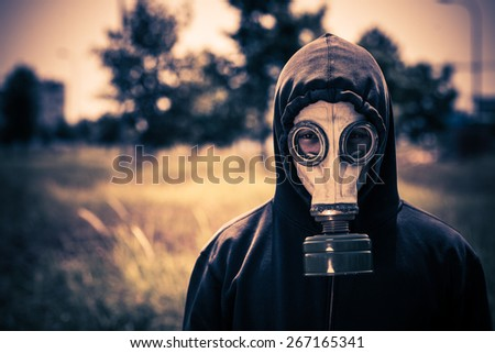 Close-up portrait of guy in gas-mask looking at the camera: ecological disaster concept #267165341