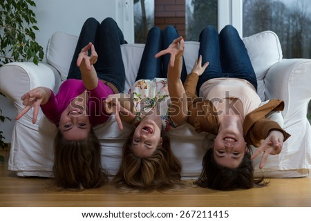 Photo of three young crazy girlfriends lying on the couch