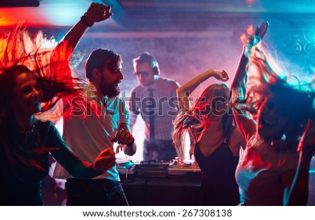 Group of dancing friends enjoying night party Royalty-Free Stock Photo #267308138