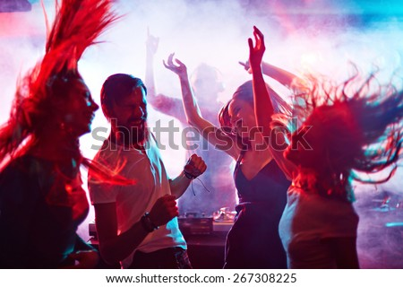 Group of energetic friends dancing in night club Royalty-Free Stock Photo #267308225