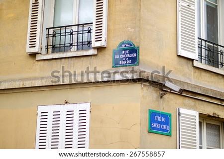 Paris classic blue street sign on a street corner, France