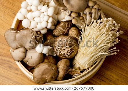 Mushrooms. Fresh Organic, enoki, shiitaki, hen of the woods, baby portabello, button mushrooms in wooden woven basket at a restaurant. Variety of Mushrooms in a basket, closeup and shot overhead. Royalty-Free Stock Photo #267579800