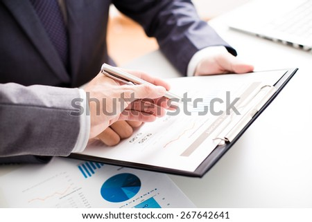 Two businessmen looking at report and having a discussion in office. #267642641