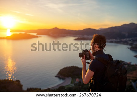 Photographer with professional photo camera and backpack on the top of the mountain on the beautiful sunset.