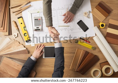 Architect and customer businessman shaking hands top view, desktop with building project, tools and wood swatches on background Royalty-Free Stock Photo #267766223