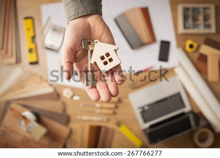 Real estate agent handing over a house key, desktop with tools, wood swatches and computer on background, top view Royalty-Free Stock Photo #267766277