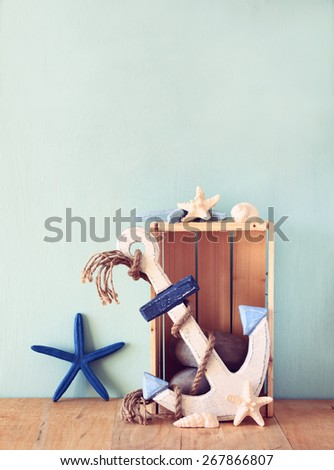 old nautical wood anchor and shells on wooden table over wooden aqua background