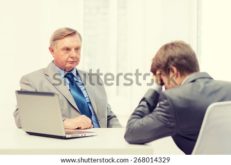 business, technology and office concept - older man and young man having argument in office Royalty-Free Stock Photo #268014329