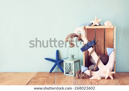 wooden anchor, star fish and lantern on wooden table. vintage filtered image