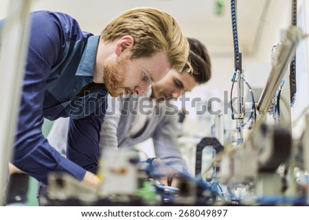 Two young handsome engineers working on electronics components and fixing broken chips #268049897