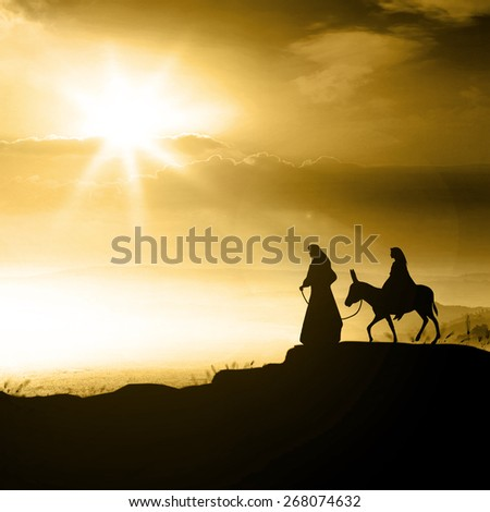 Christmas religious nativity concept: Silhouette Mary and Joseph journeying through the dessert with a donkey on golden light sunset looking for a place to stay
