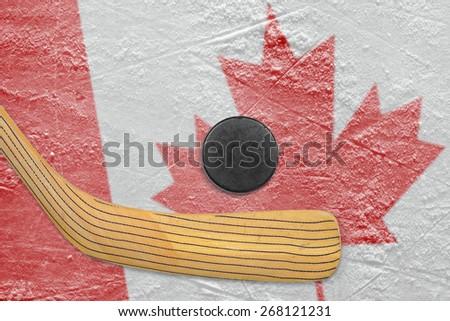 Hockey puck, hockey stick and Canadian flag image on ice