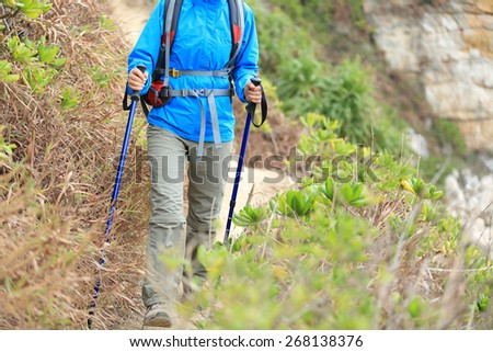 hiking woman walking on seaside mountain trail #268138376