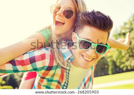 holidays, vacation, love and friendship concept - smiling couple having fun in park #268205903