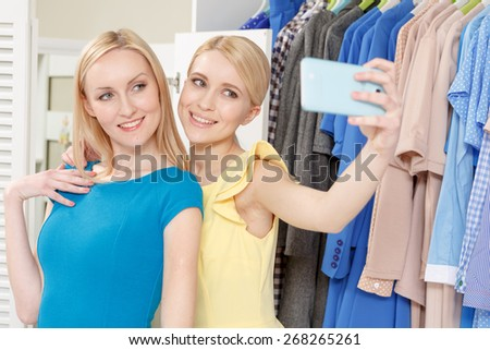Selfie from the shop. Two smiling girls making a selfie on a phone standing by clothing rack in a store #268265261