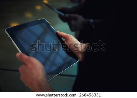 Cropped shot of male person using a digital tablet, man's hand typing text message zooming digital image on touchpad, businessman using his wireless devices during a meeting, work on a tablet screen #268456331