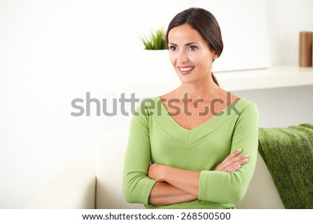 Confident young caucasian woman with arms crossed looking away and smiling at indoors - copy space #268500500