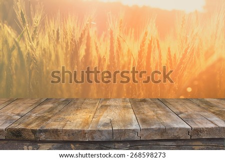 wood board table in front of field of wheat on sunset light. Ready for product display montages #268598273
