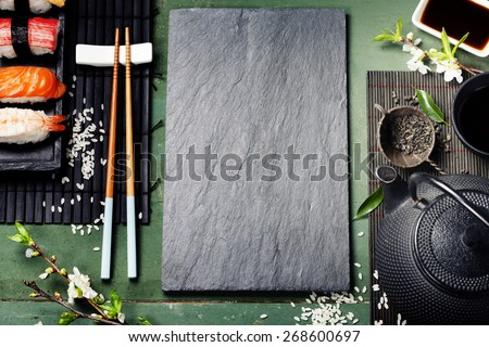 Asian food background (black iron tea set and sushi on rustic table) #268600697