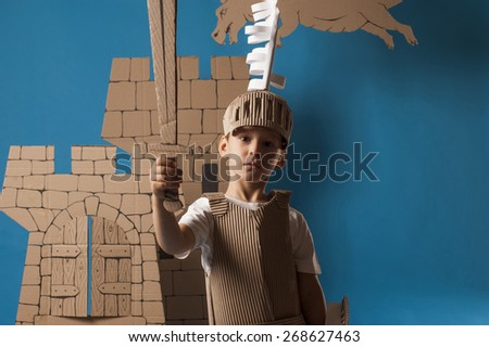 photo of the boy in medieval knight costume made of cardboards #268627463