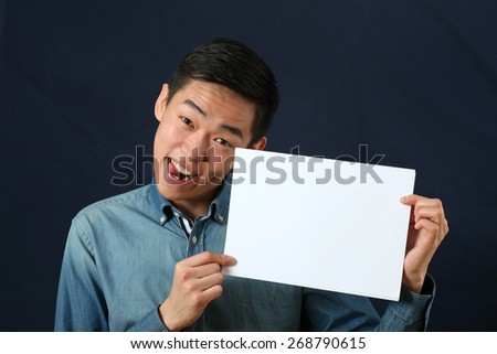 Funny young Asian man showing copy space page and looking at camera #268790615