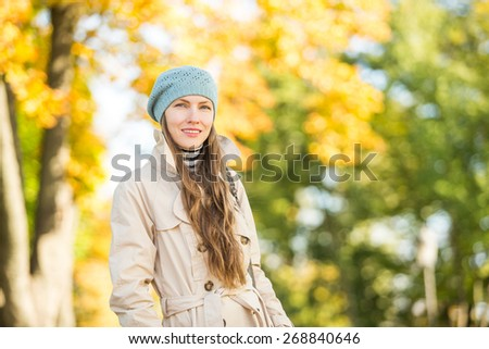 Walking in autumn park, young woman over natural autumn background #268840646