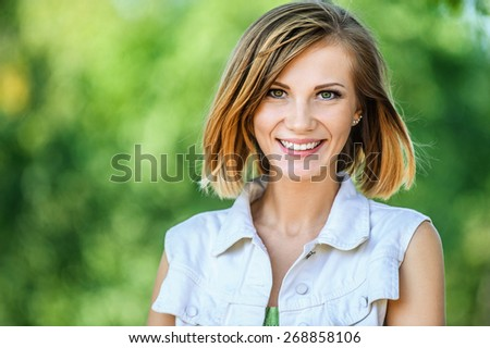 Portrait of smiling beautiful young woman close-up, against green of summer park. #268858106