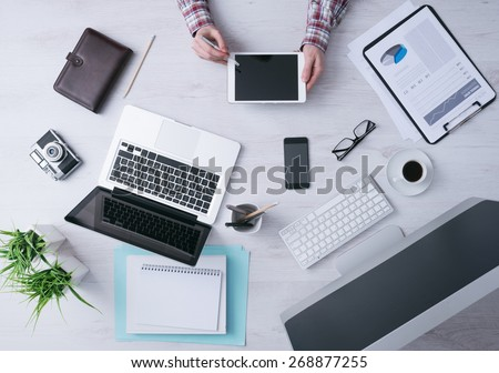 Businessman working at office desk and using a digital tablet, computer, laptop and various objects all around, top view #268877255
