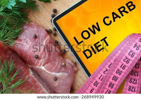 Tablet with low carb diet and fresh meat  on wooden board Royalty-Free Stock Photo #268949930