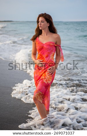 lovely brown haired young lady walking along surf on windy afternoon #269071037