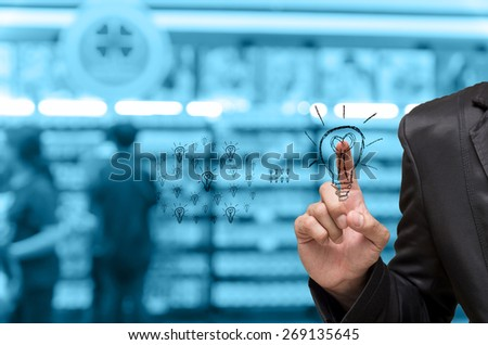 Abstract blurred photo of book store with Businessman pointing the idea on people background, blue color tone #269135645