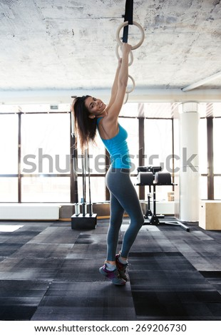 Side view portrait of a happy woman working out on gimnastic rings at gym. Looking at camera  #269206730