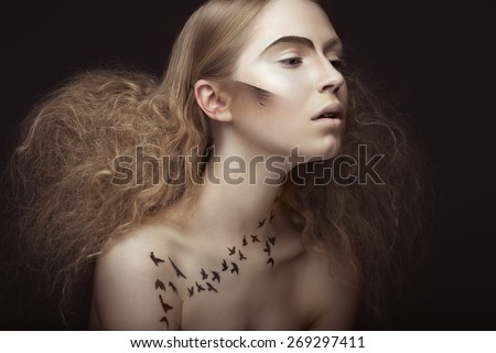 Beautiful girl with a pattern on the body in the form of birds, creative makeup and hairstyle lush. Beauty face. Picture taken in the studio on a gray background.