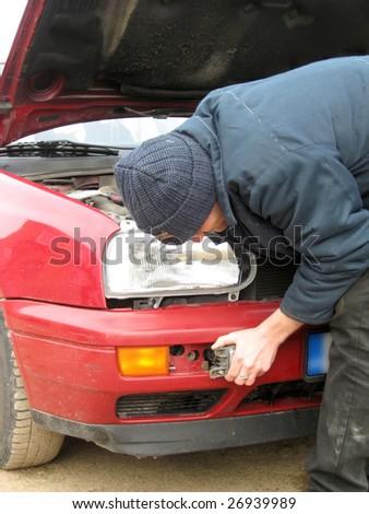 Man, repairing the car fog lights, outdoor #26939989