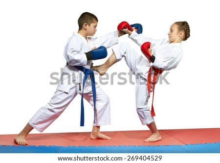 The girl with a red belt kicks the boy with a blue belt #269404529