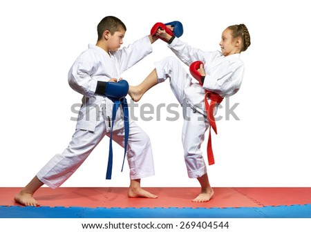 The girl with a red belt kicks the boy with a blue belt #269404544