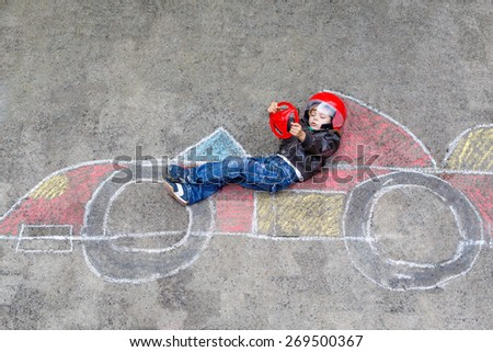 Funny kid boy having fun with race car picture drawing with colorful chalks. Creative leisure for children outdoors in summer