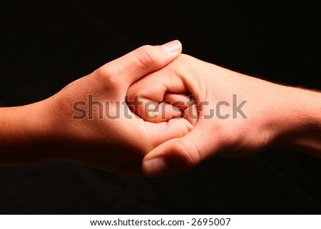 Two hands intertwined to create a Jinn Jan type symbol signifying unity and strength #2695007