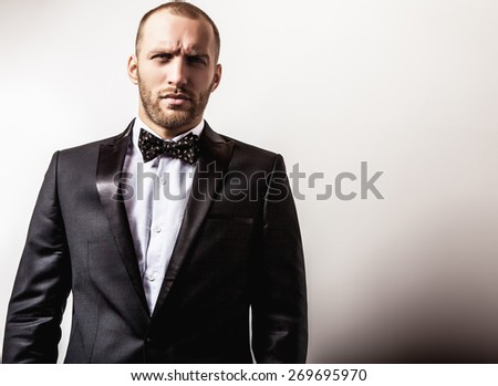 Elegant young handsome serious man in black costume. Studio fashion portrait. #269695970