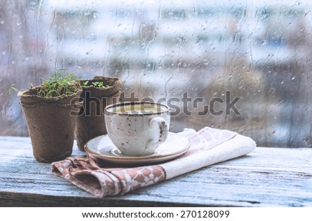 Cup with warm drink on wooden table in front of window with rain drops, rainy weather. Moody still life. Cold pale tones, horizontal image #270128099